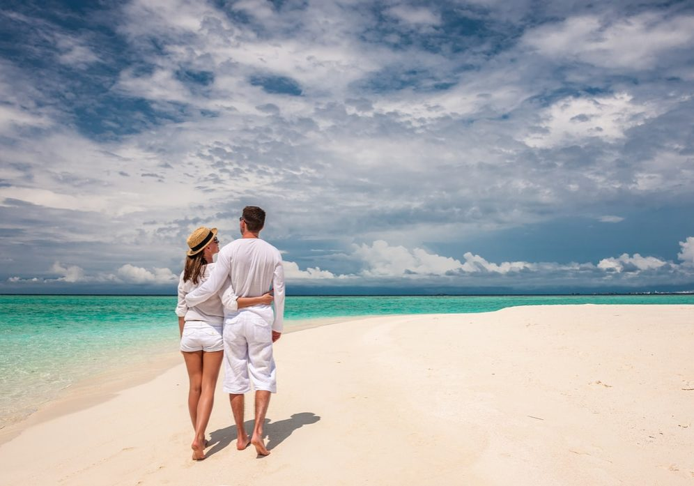 Couple In White Walking On A Beach At Maldives